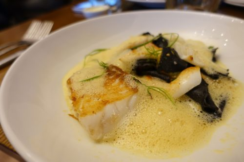Roasted cod with squid ink pasta and saffron sauce at New Chapter